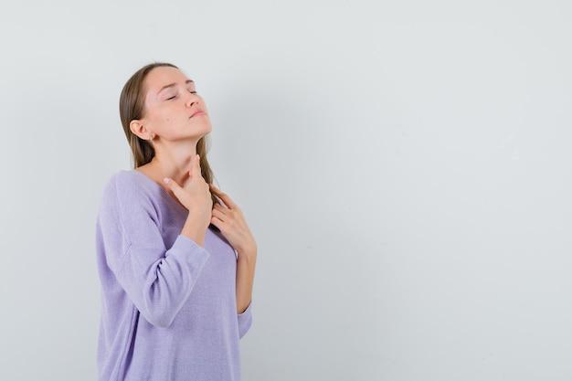 Молодая дама трогает ее шею в повседневной рубашке и выглядит мирно