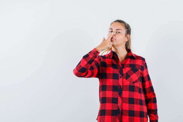 Giovane donna che tocca il naso con il dito in camicia a quadri e sembra carina