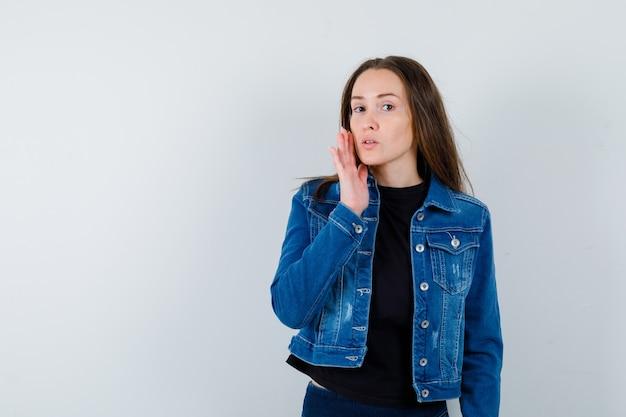 Giovane donna che tocca la pelle sulla guancia in camicetta, giacca e sembra delicata, vista frontale.
