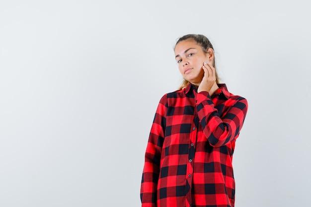 Giovane donna che tocca la pelle sulla sua guancia in camicia a quadri e sembra delicata