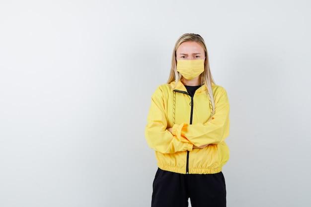 Giovane donna in tuta da ginnastica, maschera tenendo le braccia conserte e guardando sconvolto, vista frontale.