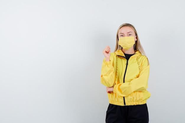 Giovane donna in tuta da ginnastica, maschera in posa stando in piedi e guardando pensieroso, vista frontale.