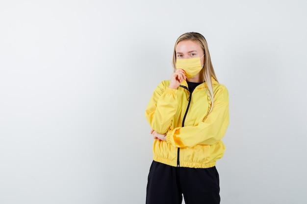 Giovane donna in tuta da ginnastica, maschera che sostiene il mento a portata di mano e che sembra pensierosa, vista frontale.