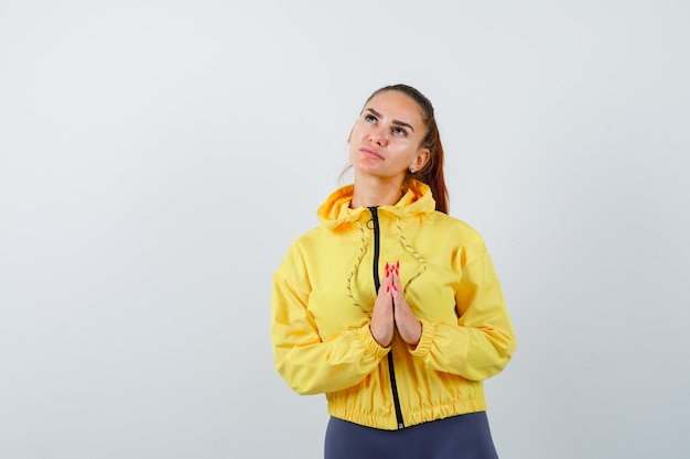 Young lady in tracksuit showing namaste gesture while looking up and looking hopeful , front view.