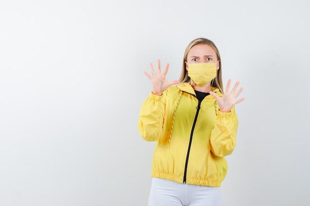 Giovane donna che cerca di bloccarsi con le mani in giacca, pantaloni, maschera e sembra terrorizzata, vista frontale.