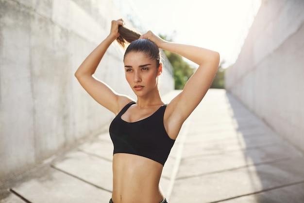 화창한 여름날 콘크리트 정글에서 매일 매일 운동하기 직전에 머리를 묶는 젊은 아가씨. 도시 스포츠 개념.