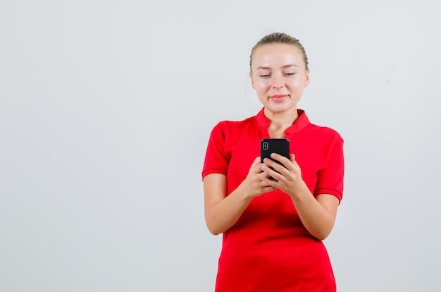 赤いtシャツを着て携帯電話で入力し、陽気に見える若い女性