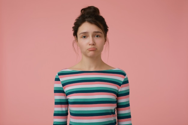 若い女性、ブルネットの髪とパンを持つ不幸な女性。縞模様のブラウスを着て唇を吐き、気分を害した。感情的な概念。パステルピンクの壁に分離