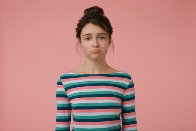 Signora giovane, donna infelice con capelli castani e chignon. indossa una camicetta a righe e fa il broncio, offeso. concetto emotivo. isolato su muro rosa pastello