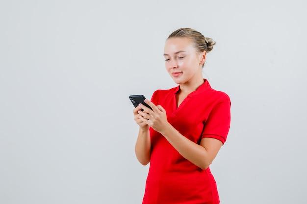 携帯電話を使用して、赤いtシャツで笑っている若い女性