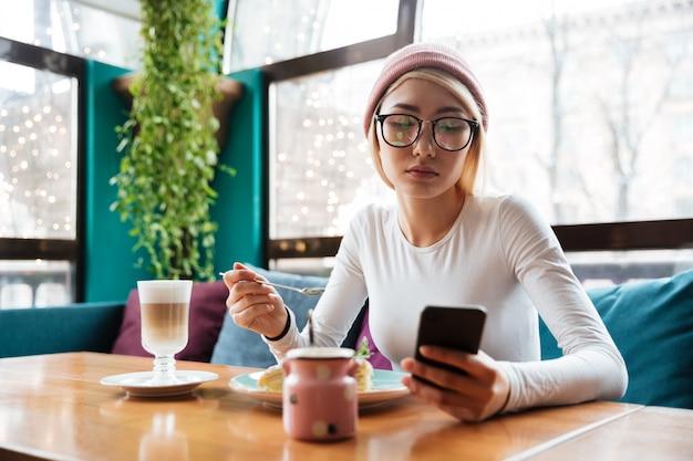 Молодая леди, с помощью телефона, пить кофе, сидя в кафе.