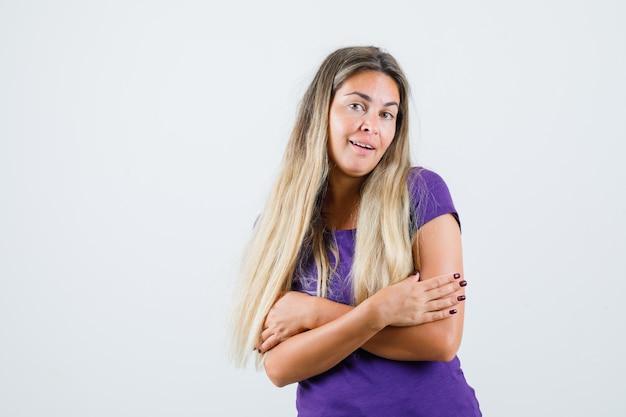 Giovane donna in maglietta viola che si abbraccia e sembra carina, vista frontale.