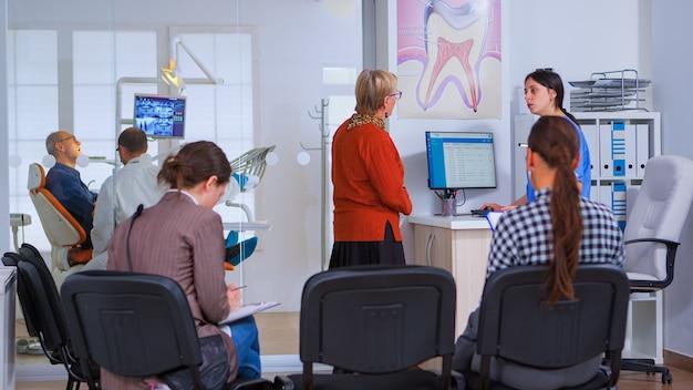 歯科医がバックグラウンドで歯科手術のために老人を準備している間、歯のチェックのために口腔病クリニックを訪れる若い女性。歯科矯正医院の混雑した待合室に座っている患者