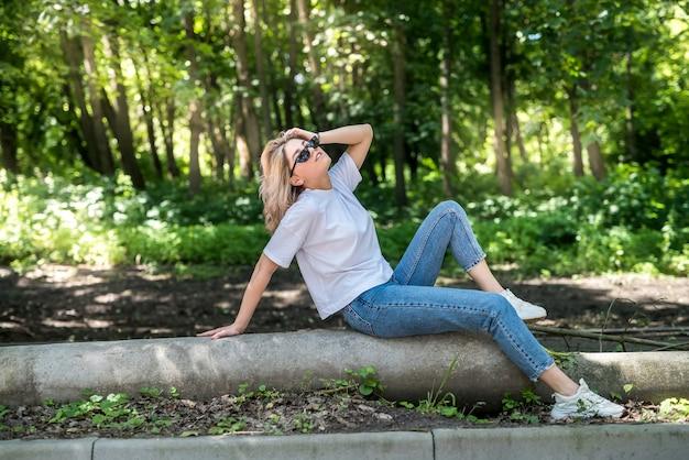 若い女性は森の中を歩き、屋外で素晴らしい時間を過ごします