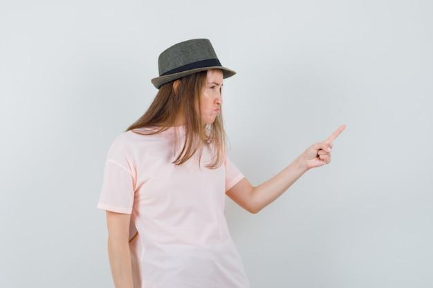 분홍색 티셔츠 모자에 손가락으로 경고하고 짓궂은 찾고 젊은 아가씨