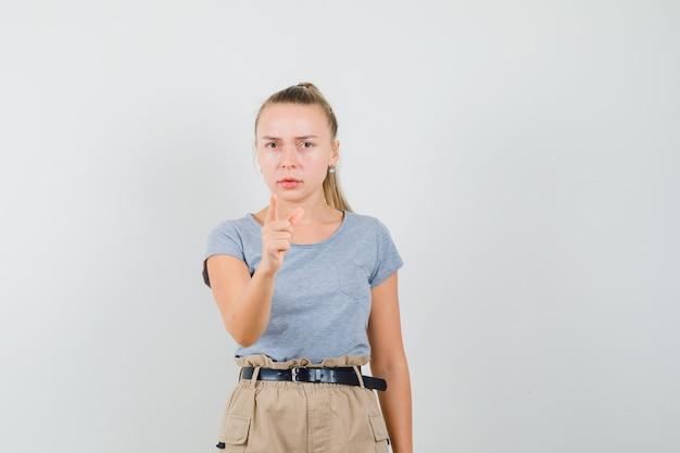 Avvertimento della giovane donna con il dito in maglietta e pantaloni e che sembra serio
