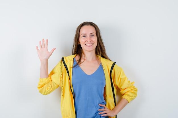 Tシャツ、ジャケットで挨拶のために手を振って、楽しく見える若い女性。正面図。