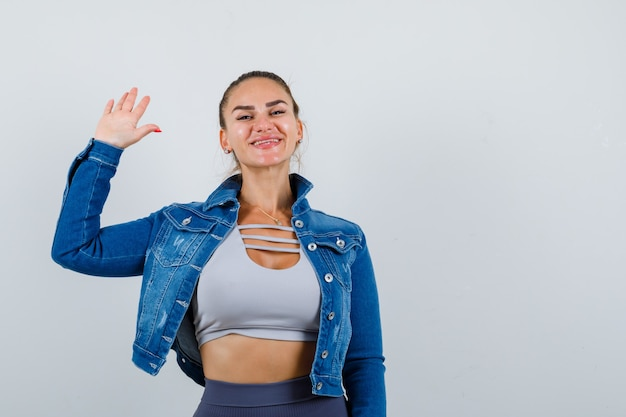 トップ、デニムジャケット、陽気に挨拶のために手を振る若い女性。正面図。