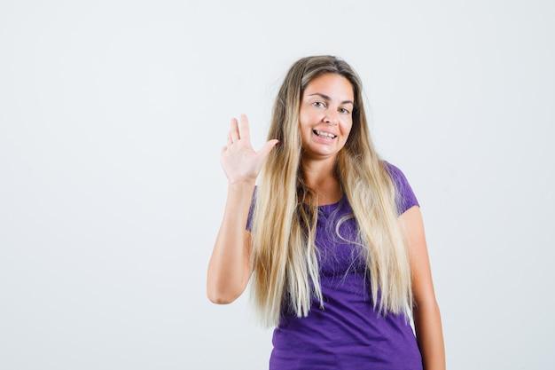 紫のtシャツで挨拶のために手を振って、陽気な、正面図を探している若い女性。