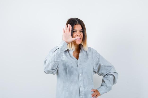 Giovane signora agitando la mano per salutare in camicia oversize e guardando felice vista frontale.