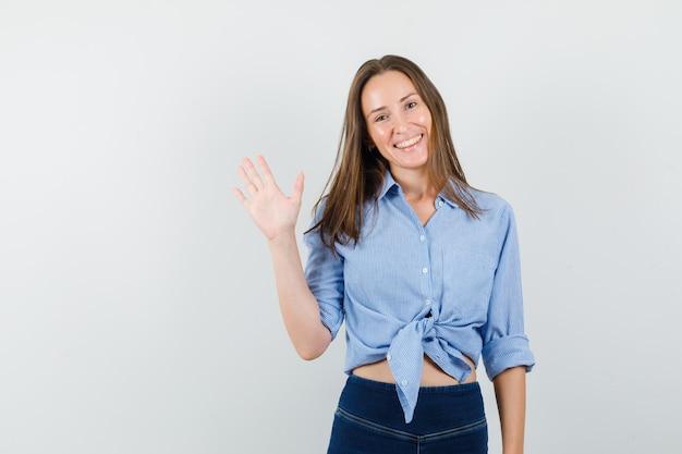 Giovane donna agitando la mano per dire addio in camicia blu, pantaloni e guardando ottimista