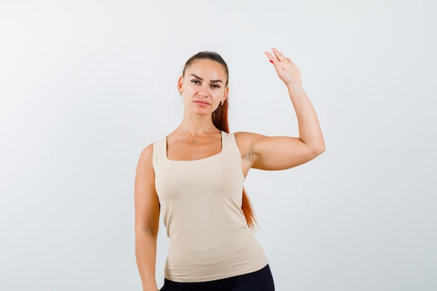 Young lady waving hand to say goodbye in tank top and looking confident. front view.