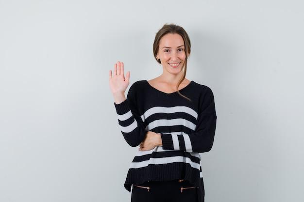 Giovane donna agitando la mano per dire ciao in camicia e guardando gioviale
