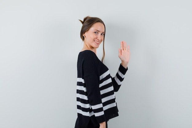 シャツを着てさよならを言うために手を振って、陽気に見える若い女性