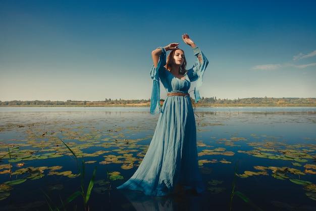 ドレスを着た若い女性が水でポーズします。