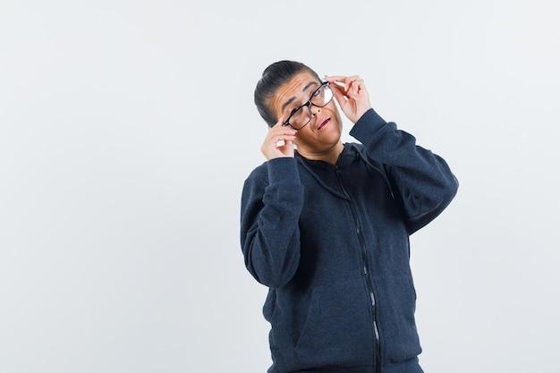 ジャケットの正面図で眼鏡をかけている若い女性。