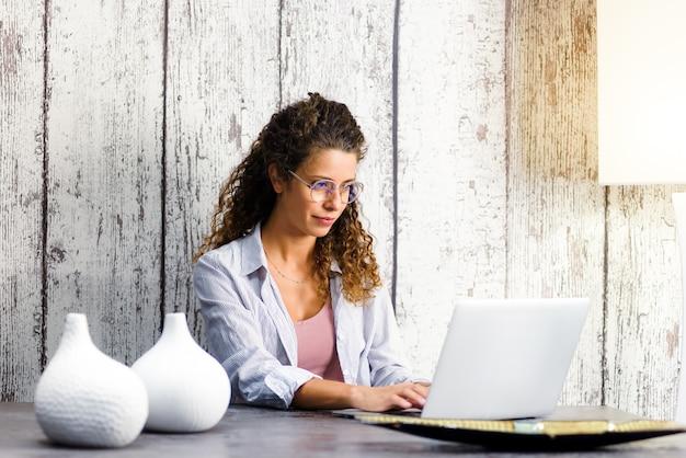 Молодая дама в очках сидит за обеденным столом удаленно, работая на ноутбуке из дома