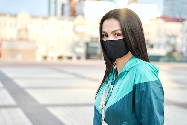 屋外のカメラでポーズをとって保護フェイスマスクを身に着けている若い女性