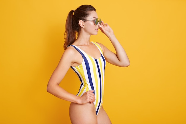 Молодая леди в полосатом купальнике, девушка с темными волосами и понитейл, позирует на желтом, смотрит в сторону и держит на руках солнцезащитные очки. копировать пространство