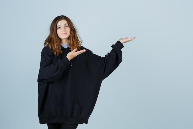 Giovane donna che dà il benvenuto in una felpa con cappuccio oversize, pantaloni e sembra sicura di sé, vista frontale.
