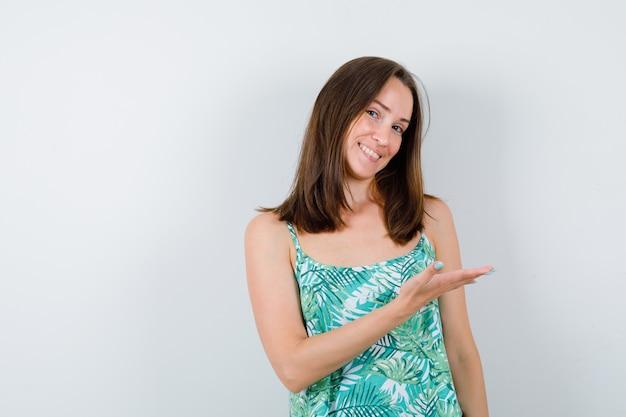 Giovane signora che dà il benvenuto a qualcosa in camicetta e sembra felice. vista frontale.