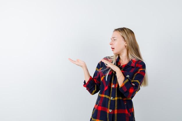 チェックシャツで何かを歓迎し、困惑しているように見える若い女性、正面図。