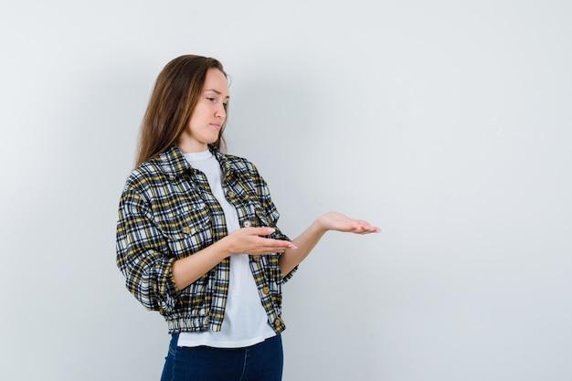 Tシャツ、ジャケット、ジーンズで何かを歓迎し、思慮深く、正面から見ている若い女性。