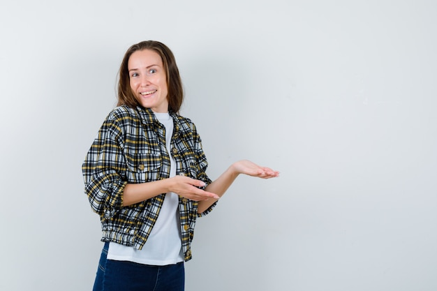Young lady welcoming something in t-shirt, jacket, jeans and looking joyful. front view.