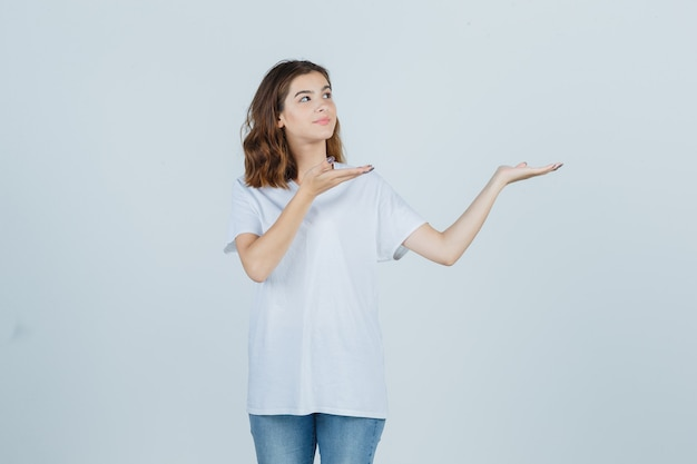 Young lady welcoming in t-shirt, jeans and looking pretty , front view.