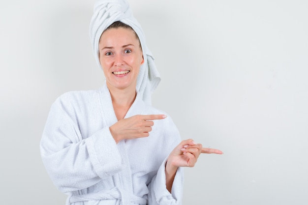 Young lady in white bathrobe, towel pointing aside and looking cheery , front view.