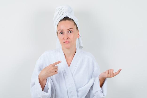 Giovane donna in accappatoio bianco, asciugamano rivolto da parte e guardando indeciso, vista frontale.
