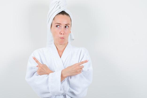 Giovane donna in accappatoio bianco, asciugamano rivolto verso l'alto mentre incrocia le braccia e sembra indeciso, vista frontale.