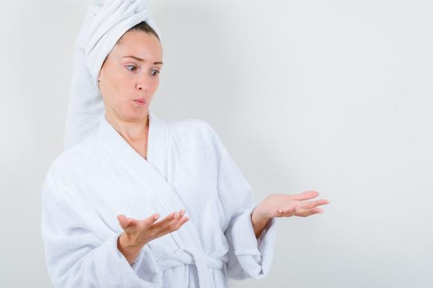 Giovane donna in accappatoio bianco, asciugamano che dà il benvenuto a qualcosa e sembra confuso, vista frontale.