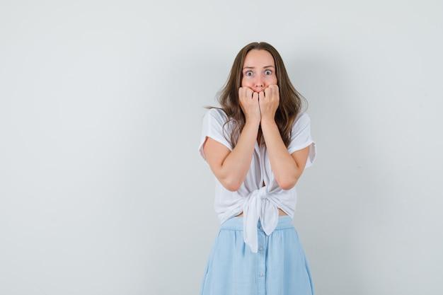Giovane donna in camicetta bianca, gonna blu che si tiene per mano sulla bocca con gli occhi spalancati e sembra spaventata