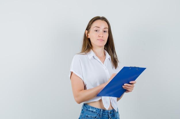 Giovane donna in camicetta bianca che tiene appunti e guardando attento, vista frontale.