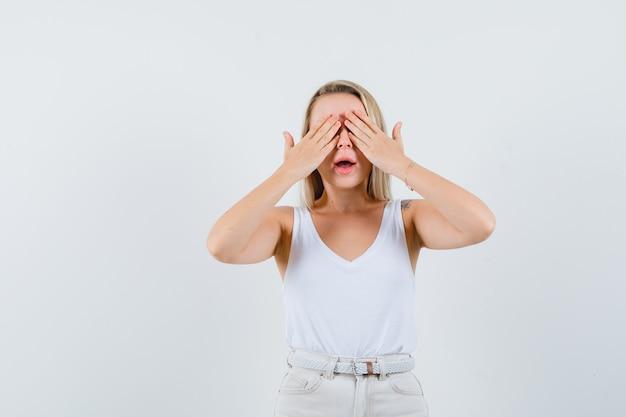 Giovane donna in camicetta bianca tenendosi per mano sugli occhi e guardando eccitato