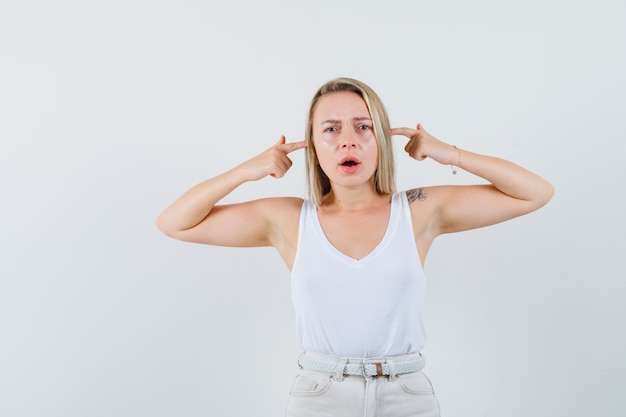 Young lady in white blouse plugging her ears with fingers and looking uncomfortable