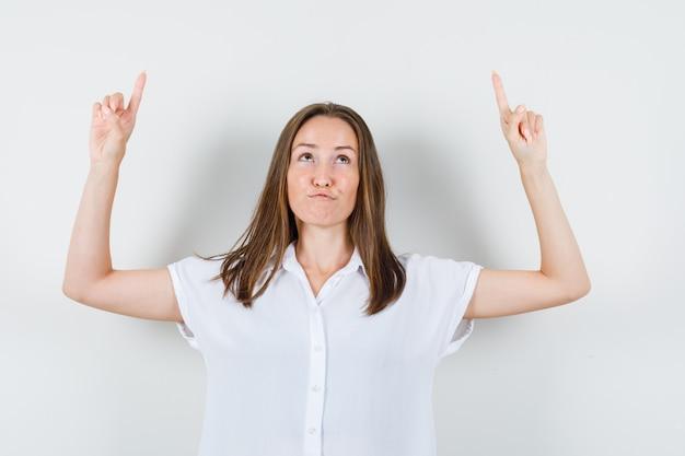 Giovane donna in camicetta bianca rivolta verso l'alto e dall'aspetto strano