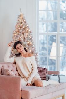 Giovane donna in abito bianco sul divano nel periodo natalizio