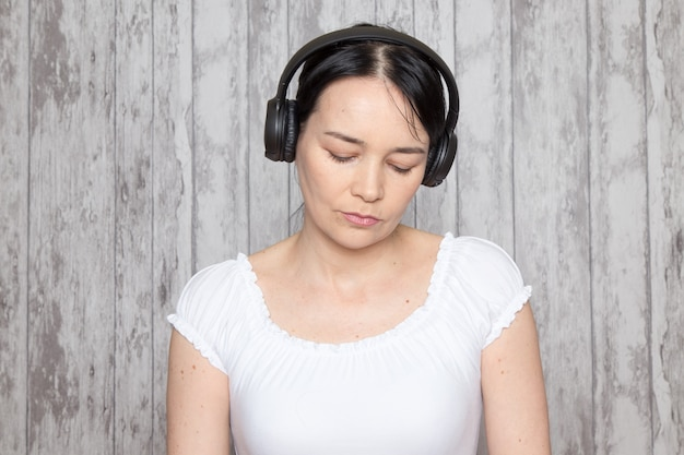 Young lady in white shirt listening to music in black earphones on grey wall